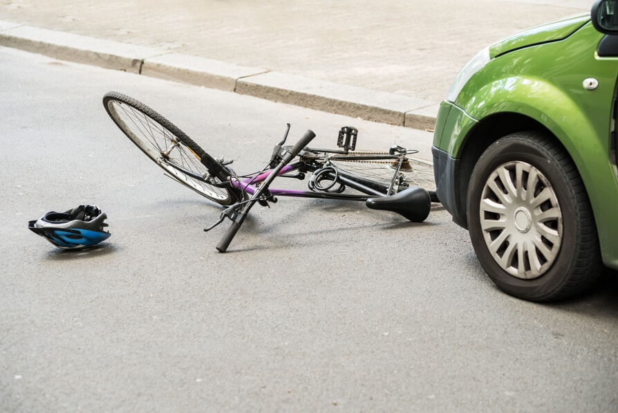 Bicycle laying on ground after a car accident